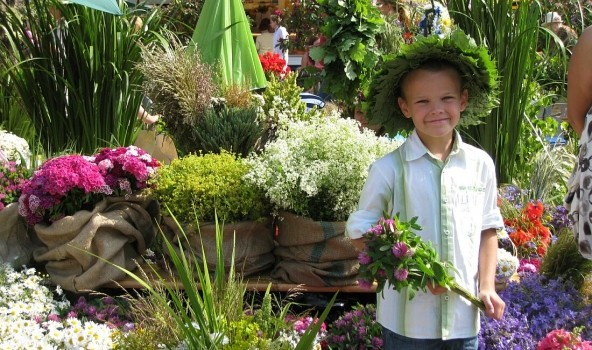 latvian boy smiling with midsummer flowers
